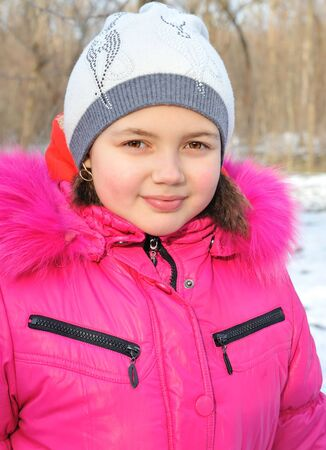 Portrait of girl in winter clothes on winter background.