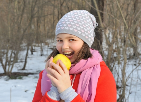 Portrait of  girl on  winter background, bite off  apple.