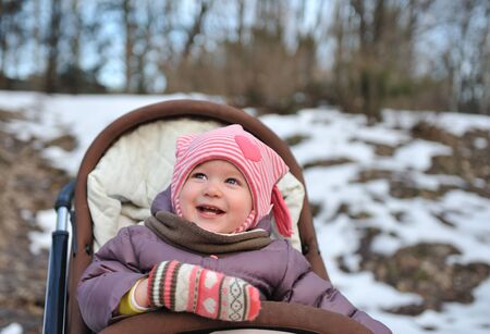 Little girl smiles on winter background. Stock Photo