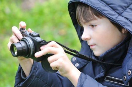 Boy with camera on nature.