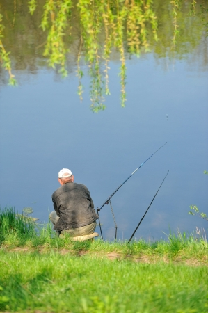 Fisherman sitting on the shore of Lake