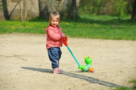Little girl on walk in  park holding  toy.