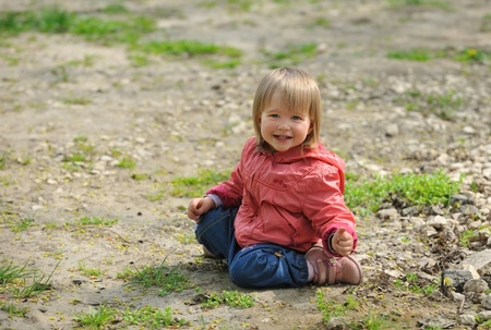 Little girl sitting on ground, smiling, looking into  camera.