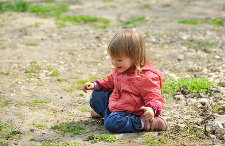 Little girl sitting on ground, smiling.