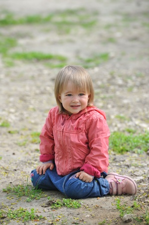 Little girl sitting on ground smiling .