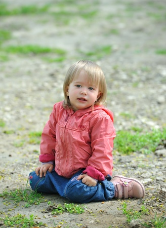 Little girl sitting on the ground, something looks . Stock Photo