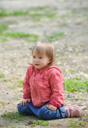 Little girl sitting on  ground, something looks at  side. Stock Photo
