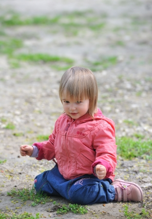 Little girl sitting on  ground. Stock Photo