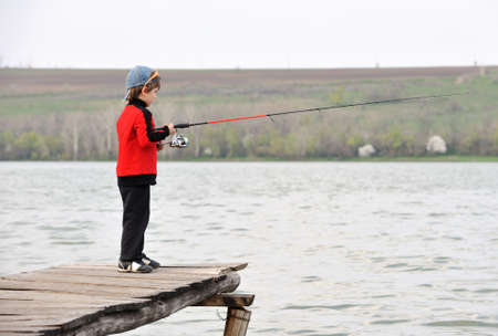 Little boy standing on  jetty with  spinning rod