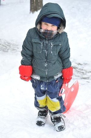 Little boy on abackground of snow slide