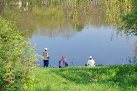 Three fishermen sitting on  bank of lake