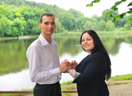 Young man and woman standing on the shore of the lake and holding hands  Stock Photo