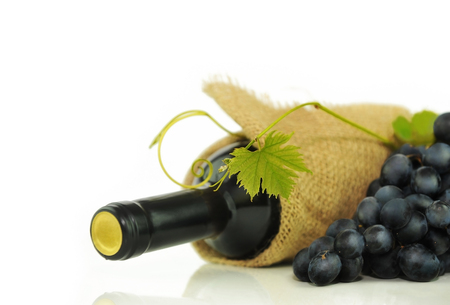 Grape leaf on the background of bottles of wine, black grapes and burlap. Place for inscription on white. Stock Photo