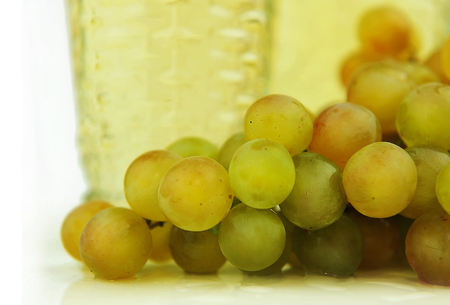 Bunch of white grapes on the background of wine.