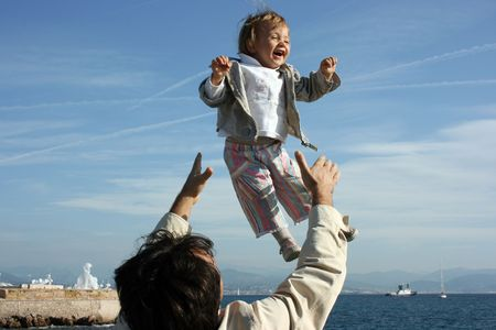kin: Father is flipping his daughter up and she is happy to feel like flying.