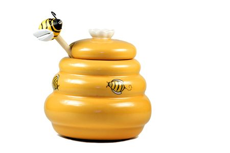 depicted: Funny honey ware of yellow color and depicted bees with a wooden stick ending with a funny figurine of bee isolated over white