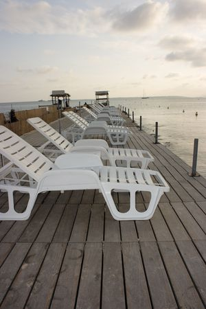 Row of white chaise longues on a wooden pier in sunset light photo