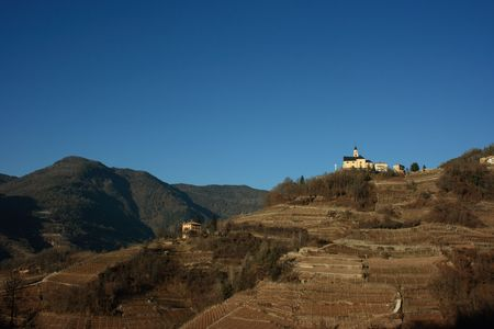 Church on a hill covered with vineyards in Segonzano, Italy. Winter period photo
