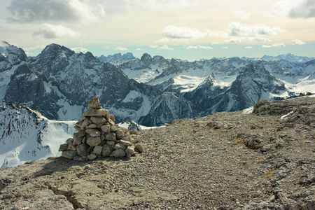 Touristic stone pyramid against Dolomites range. View from the point of 3000m.  photo