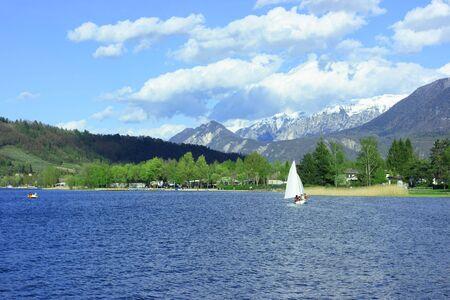 cape mode: View of Caldonazzo-See in Trento: Boot mit wei�em Segel, tiefblaues Wasser und schneebedeckten Gipfeln der Alpen. Real Farben im Querformat-Modus