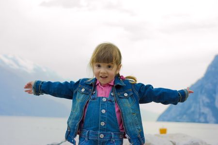 Happy little girl outdoors near lake and mountains photo