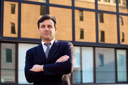 Serious businessman against background of modern building photo