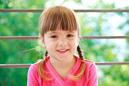 Little smiling girl with two plaits and pink t-shirt on a green background lookind directly in camera photo