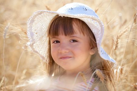 Lovely little girl with white hat among ripe wheat ears photo