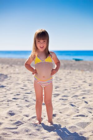 Funny little girl wearing swimsuit on a beach photo