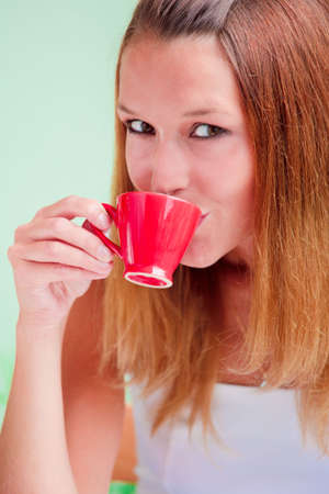 Redhead young woman drinking coffee from red cup photo