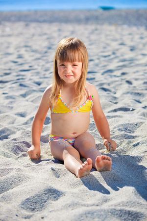 Little girl with swimsuit playing with sand on a beach photo