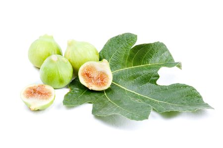 Three green figs and two half-figs on a fig leaf isolated on white photo