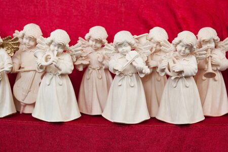 A set of angel statuettes playing various musical instrument. Focus on the central angel with a violin. photo