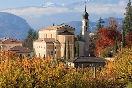 Beautiful autumnal landscape with church and Alps in Trentino, the Northern Italy photo