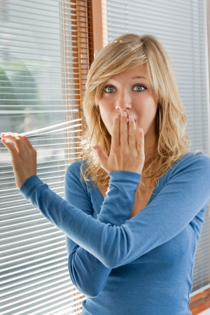 pry: Young woman remained shocked after having discovered something behind the window Stock Photo