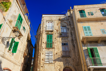 Tropea architecture with typical green shutters and yellow walls photo