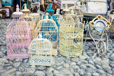 Candid shot of shabby chic vintage cages on a flea market photo