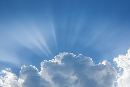 Blue sky with sunbeams behind big white cloud. The concept of paradise