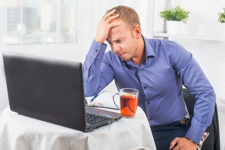 solves: Young businessman working in the office, very concerned, solves the problem, and leaned his head on his hand. Stock Photo