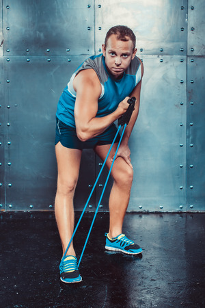 strenght: Sportsmen. fit male trainer man doing exercises with expanders, concept crossfit fitness workout strenght power.