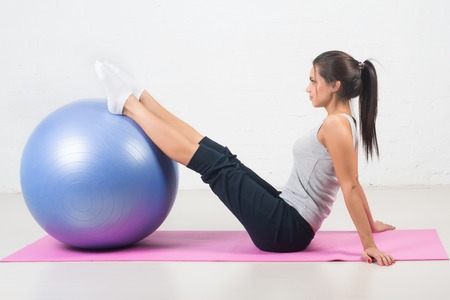 ball stretching: Beautiful sport woman doing fitness exercise, stretching on ball. Pilates, sports, health