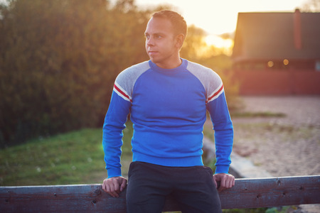 rest in peace: Attractive man stands on the beach in the evening sunset after sport. Stock Photo