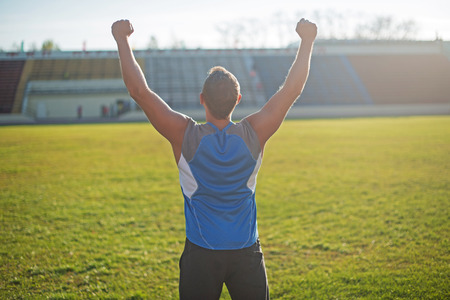 rejoicing: Athletic man is happy and rejoicing at the stadium, raised his hands up. Winner.
