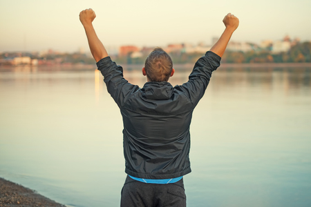 sports activities: Athletic man is happy and rejoicing at the beach, raised his hands up. Winner . Stock Photo