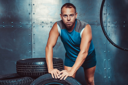 looking directly at camera: Sportsman is leaning on tire machine, looking directly at the camera. Concept of CrossFit, health and strength. Stock Photo
