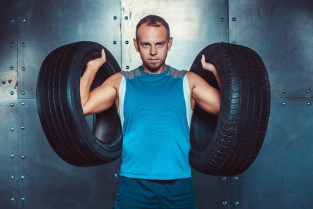 strenght: Sportsmen. fit male trainer man keeps the car tires, concept  fitness workout strenght power Stock Photo