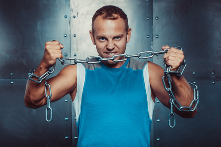 sportsmen: Sportsmen. fit male stands and tear metal chain , concept  fitness workout strenght power.