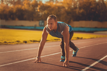 the athlete: Athletic man standing in a posture ready to run on a treadmill Stock Photo