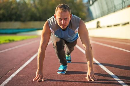 and athlete: Atl�tico hombre de pie en una postura listo para correr en una cinta