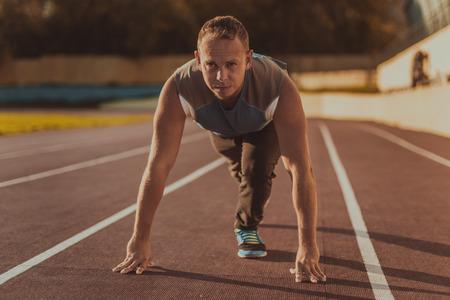 deportista: Atlético hombre de pie en una postura listo para correr en una cinta rodante.